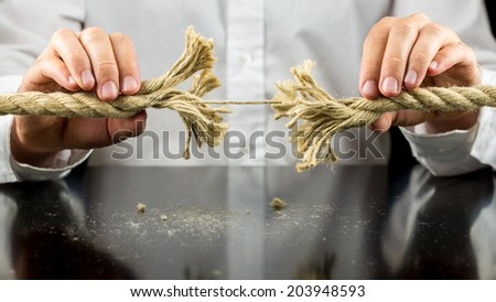 Man holding a frayed rope with one remaining string intact in both his hands in a risk and adversity concept. - stock photo