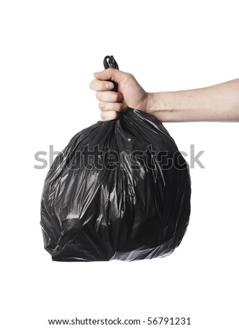 Man holding a full black plastic trash bag in his hand. - stock photo