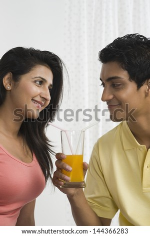 Man holding a glass of orange juice and looking at his girlfriend - stock photo