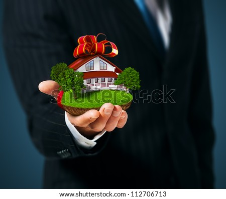 Man holding a ground with House in  hand. Gift - stock photo