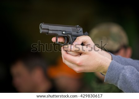 Man holding a gun in his hands is ready to shoot - stock photo