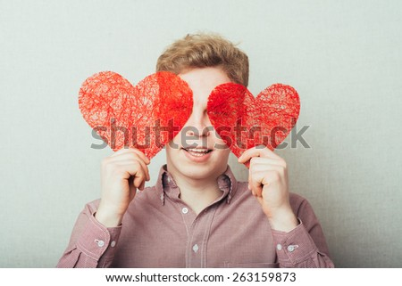 man holding a heart. It shows that love and closes her eyes hearts - stock photo