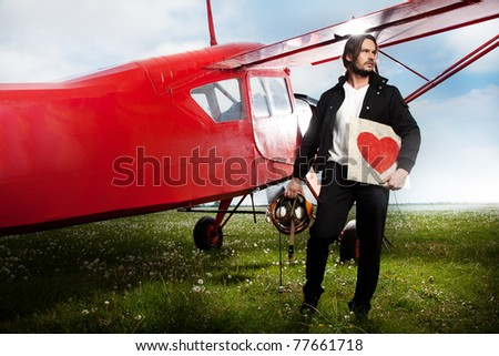 Man holding a heart symbol next to aero-plane - stock photo