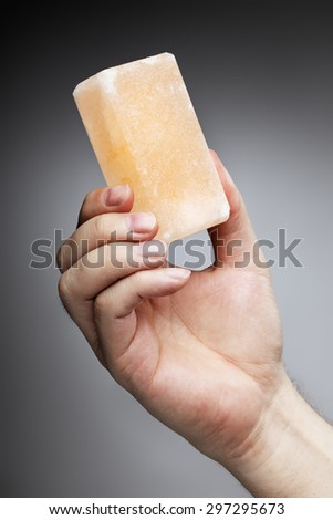 Man holding a himalayan salt soap bar, used for cleansing the skin or as a deodorant. - stock photo