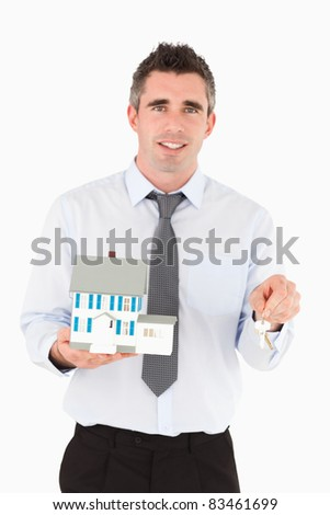 Man holding a key and a miniature house against a white background - stock photo