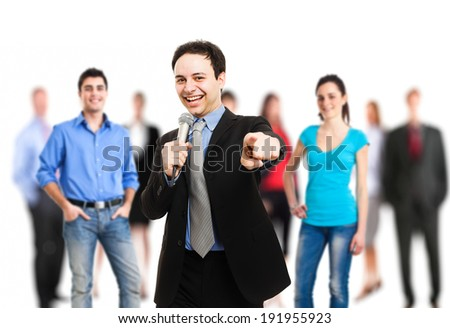 Man holding a microphone while pointing his finger at you - stock photo
