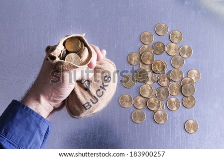 Man holding a money bag full to overflowing of Bucks with American dollar coins lying strewn on the table below in a concept of greed, wealth, investment or gambling at a casino, overhead view - stock photo