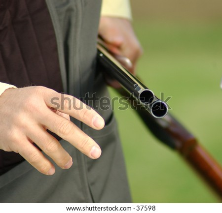 man holding a open shotgun on a trap range - stock photo
