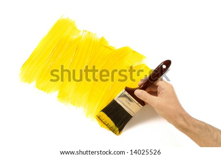 Man holding a paintbrush with a partly finished yellow painted wall.  Space for copy. - stock photo