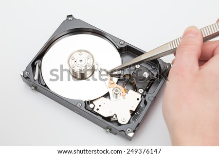 man holding a pair of tweezers to open the hard drive - stock photo