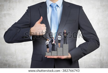 man holding a pedestal in the shape of a bar chart, four businesspeople standing on it. Front view, no head. Concrete background. Concept of career growth. - stock photo