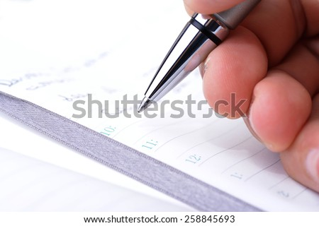 Man holding a pen over an appointment book - stock photo