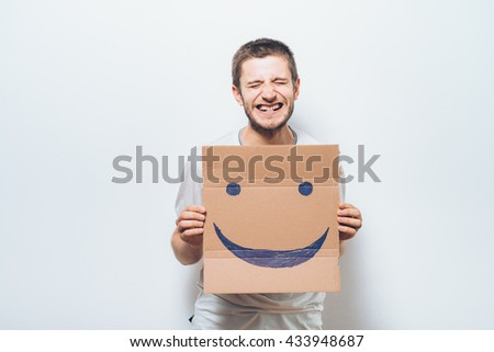 man, holding a picture with a cheerful smiley - stock photo
