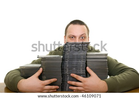 man holding a pile of CDs on the table - stock photo