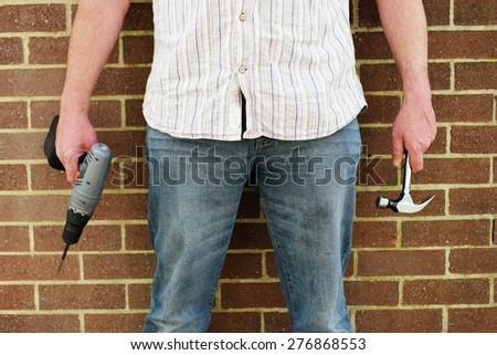 Man holding a portable battery operated drill and hammer standing in front of a brick wall, close up torso view in a DIY and construction concept - stock photo