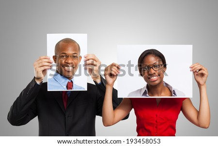 Man holding a portrait of another smiling person - stock photo