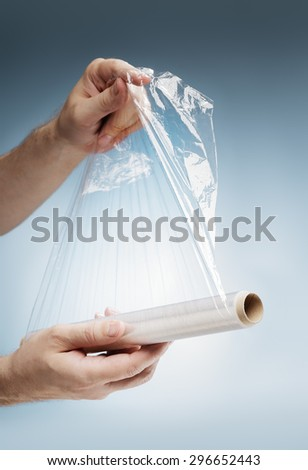 Man holding a roll of plastic film, typically used for sealing food items. - stock photo