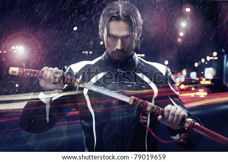 Man holding a samurai sword on a night city street - stock photo