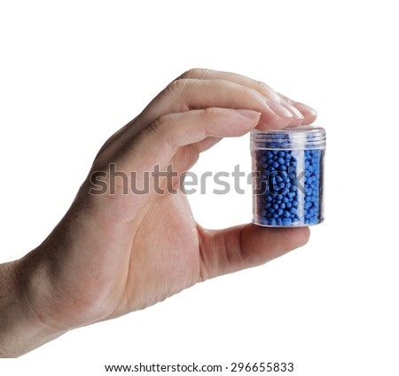 Man holding a small container with blue plastic granules, used for manufacturing. - stock photo