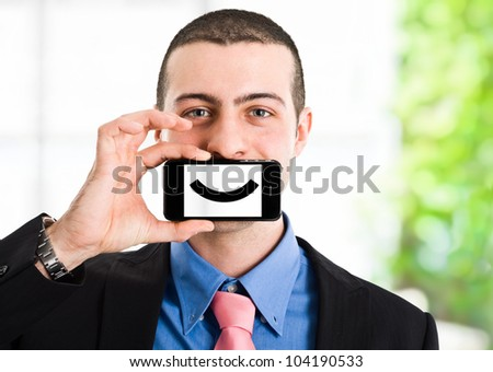Man holding a smartphone with a smile on the screen - stock photo