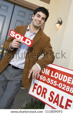 Man holding a sold sign board while standing in front of a new house - stock photo