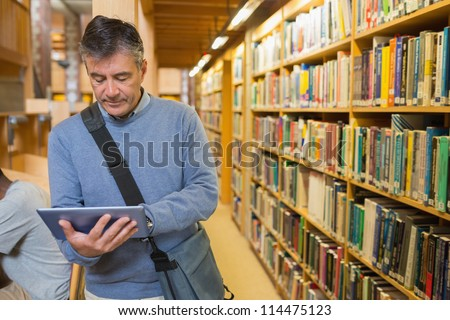Man holding a tablet pc amongst shelves in a library - stock photo