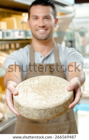 Man holding a wheel of cheese - stock photo