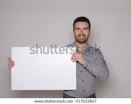 man holding a white cardboard isolated on gray background - stock photo