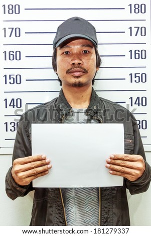 Man holding a white paper taking criminal mug shot  - stock photo