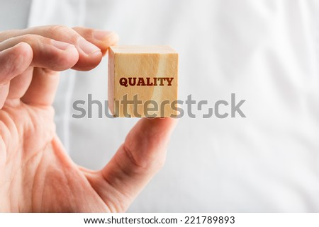 Man holding a wooden block reading - Quality, close up of his hand with copyspace over his white shirt in a conceptual image. - stock photo