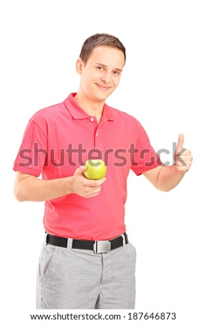 Man holding an apple and giving thumb up isolated on white background - stock photo