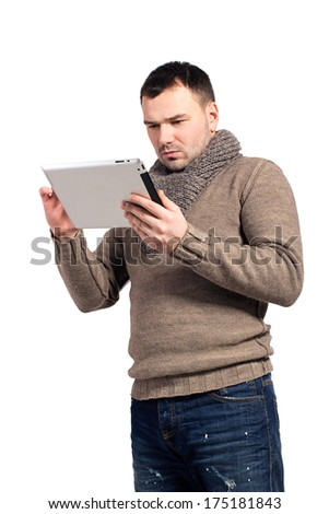 Man holding an electronic writing tablet. Young businessman working on his electronic tablet. Realtor and insurance records data in email client address book. Man looks, reads in pad. Space for text. - stock photo