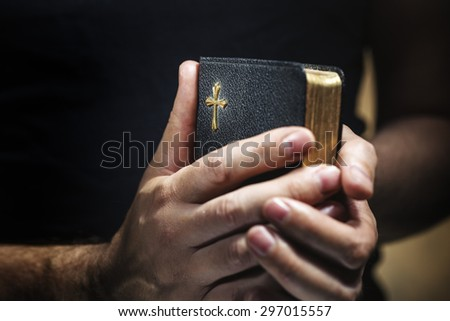 Man holding an old small black bible in his hands. Short depth of field, the sharpness is in the cross. - stock photo