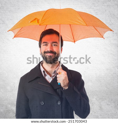 Man holding an umbrella over textured background - stock photo