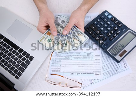 Man holding and counting money at the table - stock photo