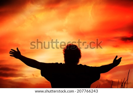 Man holding arms up in praise - stock photo