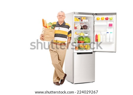 Man holding bag with groceries by an open fridge isolated on white background - stock photo