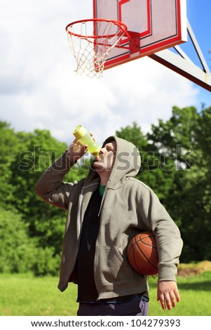 Man holding basketball and drink from bottle of water - stock photo