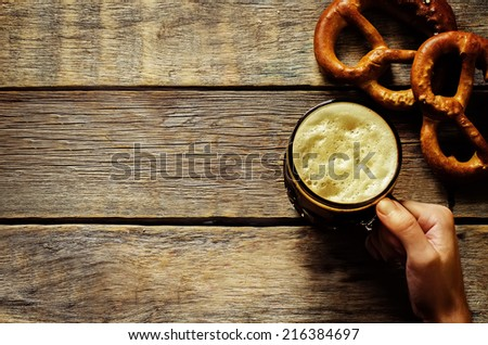 man holding beer and pretzel on a dark wood background. tinting. selective focus on the foam in the glass - stock photo