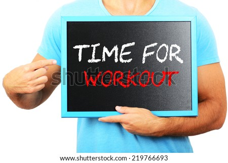 Man holding blackboard in hands and pointing the word TIME FOR WORKOUT - stock photo