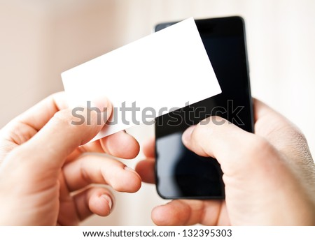Man holding blank business card and dialing numbers on mobile phone - stock photo