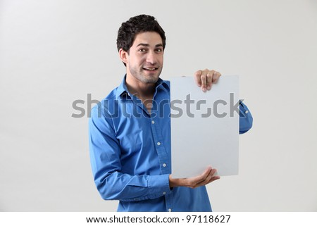 Man holding blank paper and looking at camera - stock photo