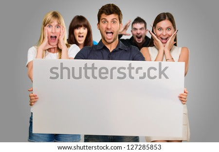 Man Holding Blank Placard And Woman Screaming From Behind On Gray Background - stock photo