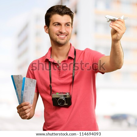 Man holding boarding pass and airplane, outdoor - stock photo
