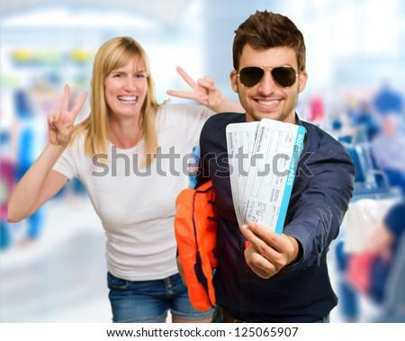 Man Holding Boarding Pass In Front Of Happy Woman Gesturing, Indoor - stock photo