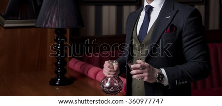 Man holding bottle and glass in his hands - stock photo