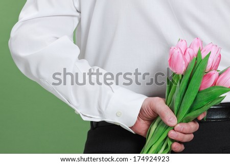 Man holding bouquet of tulips behind his back. - stock photo