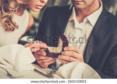 Man holding box with ring making propose to his girlfriend - stock photo