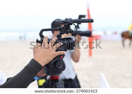 Man holding camcorder and camera working on recording a beach Polo Tournament sport - stock photo