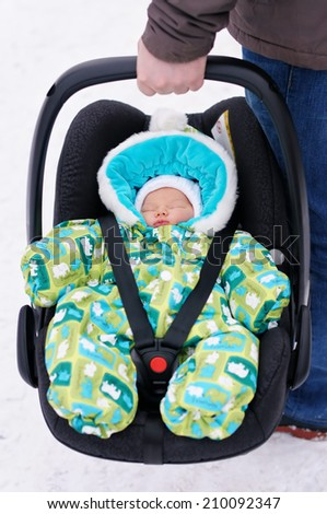 Man holding car seat with his newborn baby - stock photo